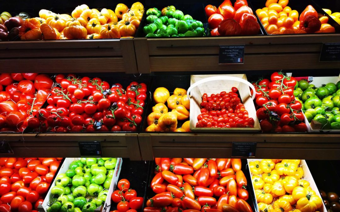 Containers of colorful vegetables in a grocery store produce section