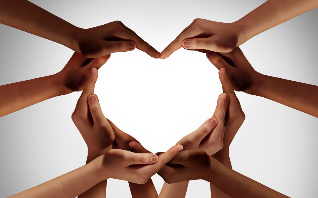 Hands of all races joining to make a heart.